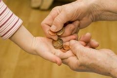 Main de grand-mère et d'enfant avec de l'argent Images libres de droits