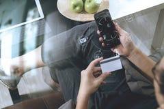 main de hippie utilisant le compter futé de téléphone et d'ordinateur portable, tenant le cradit Image stock