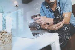 main de hippie utilisant le compter futé de téléphone et d'ordinateur portable, tenant le cradit Photos libres de droits