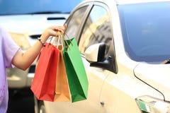 Main de jeune femme tenant des sacs à provisions sur le fond de parking de voiture images libres de droits