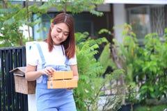 Main de jeune femme tenant la boîte brune de colis à la maison, embarquant images stock