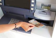Main de jeune femme tout en retirant des billets de banque d'une atmosphère dans e Photos libres de droits