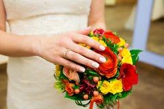 Main de jeune mariée avec l'anneau et le bouquet coloré de mariage Photos libres de droits