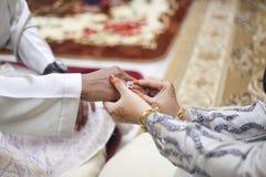Main de jeune mariée mettant un anneau de mariage sur le doigt de marié Photo libre de droits