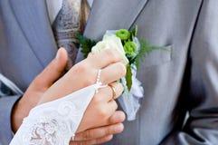 Main de jeunes mariés avec la boucle de mariage Photographie stock libre de droits