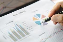 Main de l'écriture d'homme d'affaires sur le papier dans le bureau, graphiques donnant les résultats de leur travail d'équipe réu images libres de droits