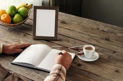 Main de l'écriture de l'homme dans un carnet vide Images stock