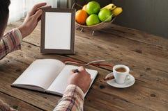 Main de l'écriture de l'homme dans un carnet vide Photographie stock libre de droits