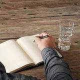 Main de l'écriture de l'homme quelque chose dans le carnet vide Images stock
