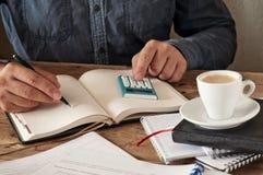 Main de l'écriture de l'homme quelque chose dans le carnet vide sur le bureau en bois Images libres de droits