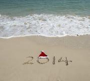 Main de l'année 2014 écrite sur le sable blanc i Images stock