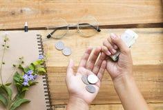Main de l'argent liquide de compte de fille, pièces de monnaie avec le carnet pour le travail d'affaires images stock