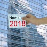Main de l'homme d'affaires tenant une note de papier avec le nouveau en 2018 te Photos stock