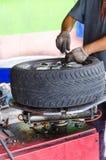 Main de l'homme enlevant le pneu de voiture image stock