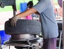 Main de l'homme enlevant le pneu de voiture photos libres de droits
