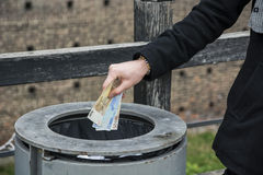 Main de l'homme jetant dehors des billets de banque dans une boîte Photographie stock