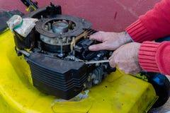 Main de l'homme réparant le vieux coupeur d'herbe avec des outils sur le plancher de ciment Réparation du moteur de tondeuse à ga images stock
