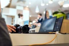 Main de l'opérateur d'appareil-photo touchant un DSLR moderne photos stock