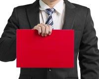 Main de l'utilisation une d'homme d'affaires pour tenir un conseil rouge vide dans le dos de blanc Photo libre de droits