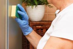 Main de la femme supérieure employant l'éponge et essuyant la porte en verre de douche dans la salle de bains, concept de fonctio Photographie stock