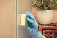 Main de la femme supérieure employant l'éponge et essuyant la porte en verre de douche dans la salle de bains, concept de fonctio Photos libres de droits
