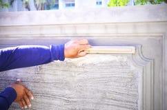 Main de la truelle d'utilisation de travailleur de constructeur plâtrant le béton Images stock
