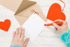 Main de lettre d'amour d'écriture de fille le jour de valentines de saint Handma image stock