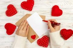 Main de lettre d'amour d'écriture de fille sur Valentine Day carte postale faite main La femme écrivent sur la carte postale pour Photos stock