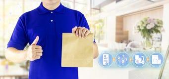 Main de livreur tenant le sac de papier dans des m?dias bleus d'uniforme et d'ic?ne pour fournir le service de distribution en li photo libre de droits