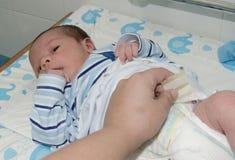 Main de mère changeant la couche-culotte nouveau-née de bébé sur le commutateur de bébé photo stock