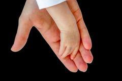 Main de mère tenant le bras du bébé sur le noir photos libres de droits