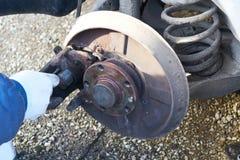 Main de mécanicien pendant l'entretien d'un frein de calibre d'une voiture Photographie stock