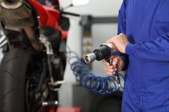 Main de mécanicien tenant une arme à feu pneumatique image libre de droits