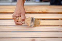 Main de Man's tenant une brosse appliquant la peinture de vernis sur un en bois image stock