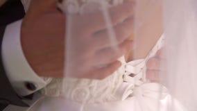 Main de marié frottant le coffre de jeunes mariées banque de vidéos