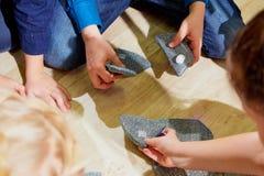 Main de morceaux et d'enfants de puzzle de chiffon les liant photo stock