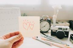 Main de note de courrier de prise de femme avec le coeur de couples et l'autobus d'équipement Images stock