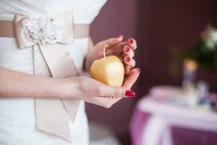 Main de nouveaux mariés avec la pomme d'or Photo stock