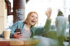 Main de ondulation de fille blonde heureuse à l'ami sur la rue Images libres de droits