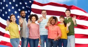 Main de ondulation de personnes internationales et drapeau américain Photos libres de droits