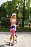 Main de ondulation de scooter d'équitation de jeune fille aux amis Images libres de droits