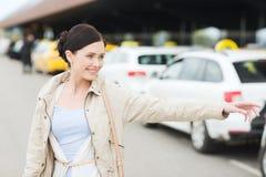 Main de ondulation de sourire de jeune femme et taxi contagieux Photos stock