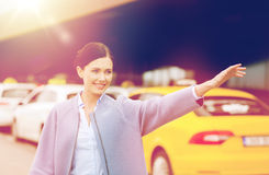Main de ondulation de sourire de jeune femme et taxi contagieux Photographie stock