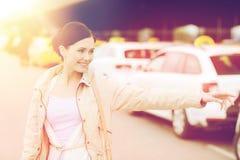 Main de ondulation de sourire de jeune femme et taxi contagieux Photos libres de droits