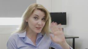 Main de ondulation de jeune femme d'entreprise gaie indiquant le bonjour dans le bureau - clips vidéos