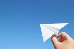 Main de papier d'avion et de mâle dans le ciel bleu Photo stock
