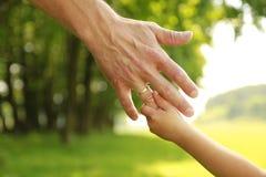 Main de parent et d'enfant en nature Photo libre de droits