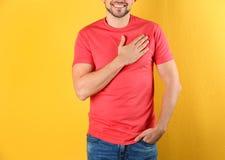 Main de participation d'homme pr?s de son coeur sur le fond de couleur image stock