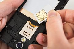Main de personne avec la carte et le téléphone portable de sim Photos stock