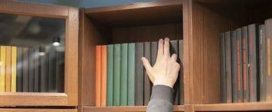 Main de personne recherchant un livre à la maison sur des étagères à livres n photographie stock libre de droits